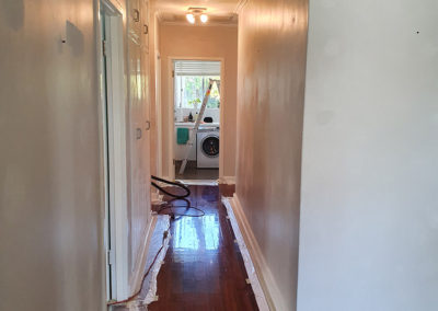 the hall way of a house with the skirting boards and door jams masked with tape before the walls are painted
